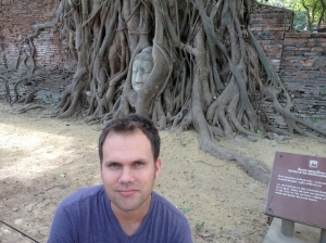 Bjorn squats in front of the Buddha head entwined in tree roots at Wat Mahathat, Ayutthaya, Thailand. (Photo by Jammie Karlman)