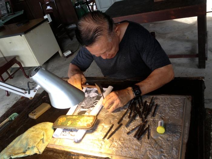 An artisan engraves a metal sheet at Ancient Siam in Samutprakan, Thailand. (Photo by Bjorn Karlman)