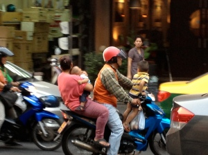 A family rides a motorbike along the streets of Bangkok, Thailand. (Photo by Bjorn Karlman)
